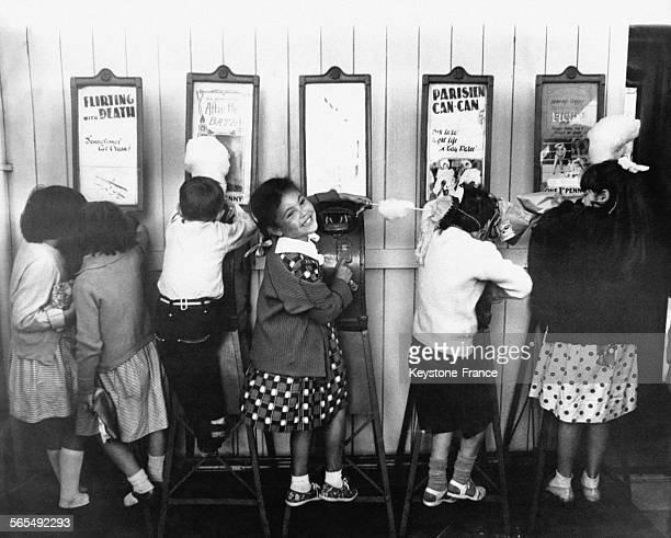 Enfants regardant des extraits de reportages dans des machines à sous dans une fête foraine aux EtatsUnis circa 1960