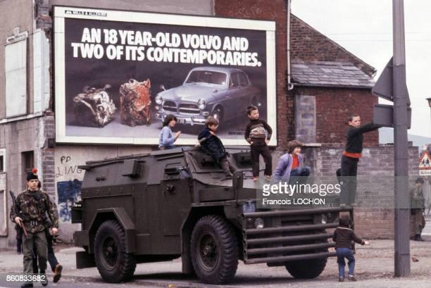 Enfants sur un tank de la police antiémeute circa 1980 à Belfast en Irlande du Nord