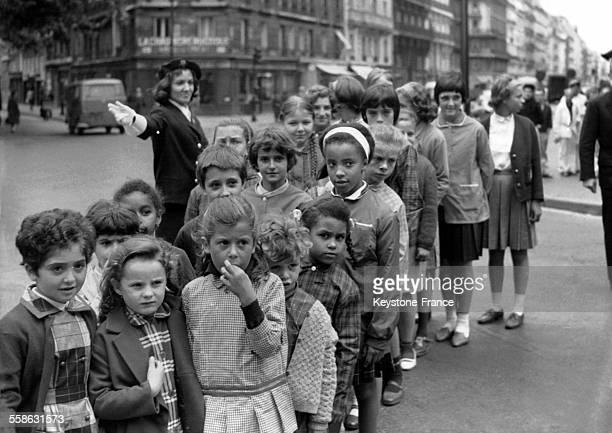 Enfants traversant les passages cloutés le jour de la rentrée scolaire sous la surveillance d'un agent de la circulation femme à Paris France le 18...
