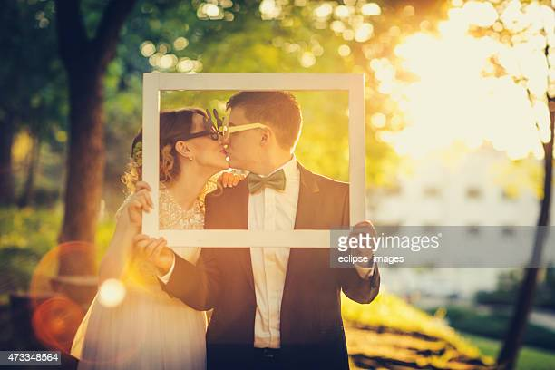 Engaged couple frames their kissing at sunset