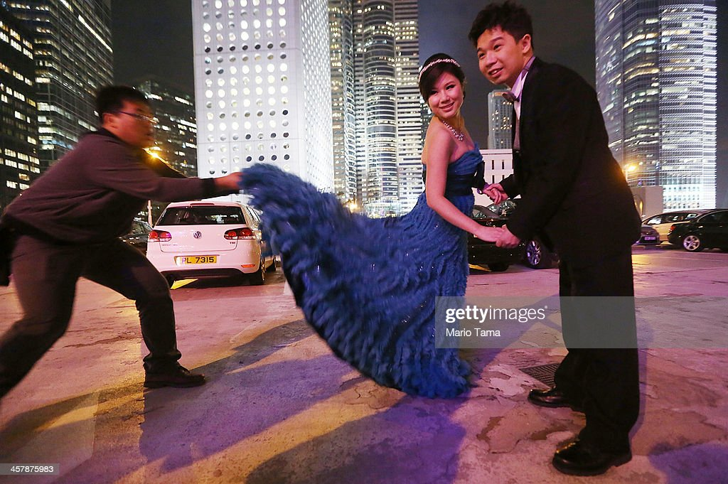 Engaged couple Tommy Ho (R) and Cindy Lai (C) pose for their wedding photographer as an assistant fluffs Lai's dress on December 19, 2013 in Hong Kong, China. Hong Kong leads the world in economic freedom according to the Heritage Foundation.