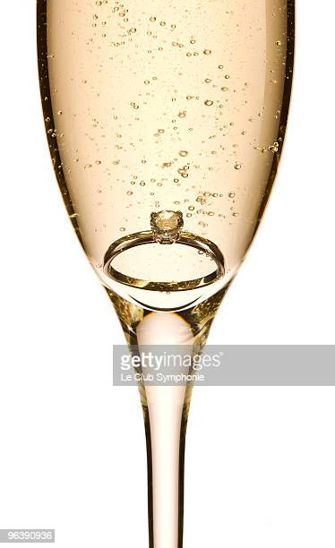 Engagement ring in glass of champagne