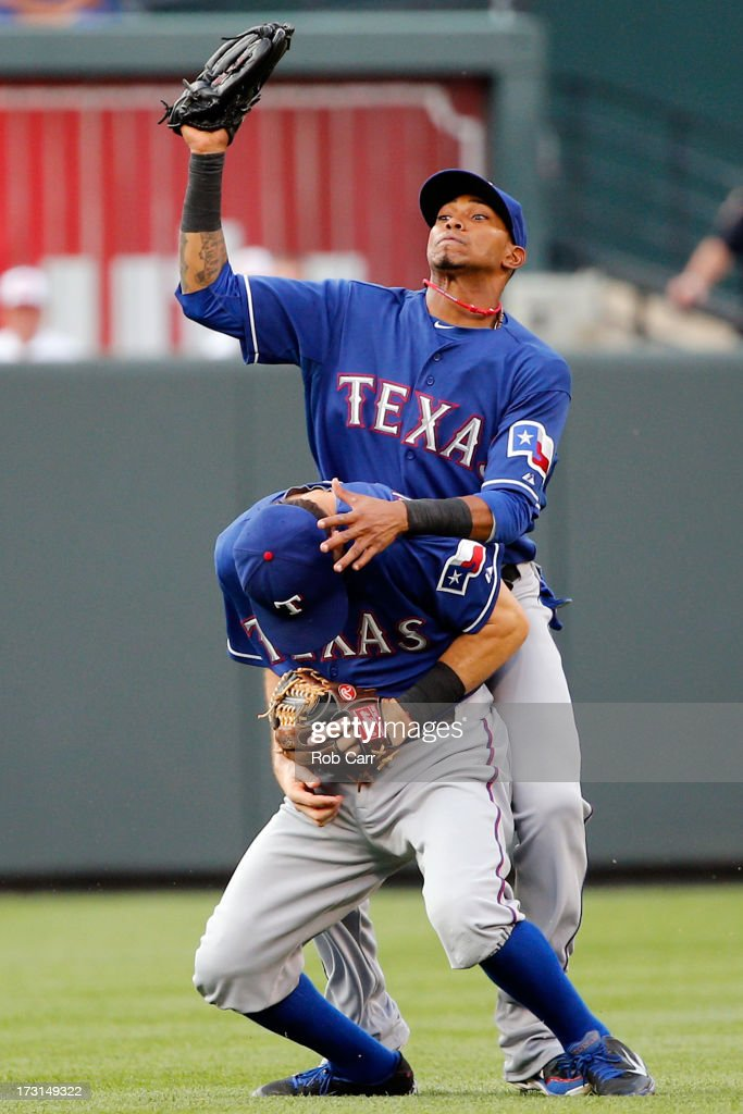 Engel Beltre of the Texas Rangers almost collides with teammate Ian Kinsler while catching a ball hit by Brian Roberts of the Baltimore Orioles for...