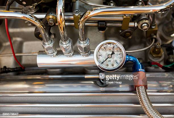 Engine compartment of antique hot rod car with focus on pressure gauge on oil piping on the engine block