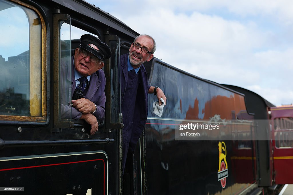 Engine driver Gerry Skelton (L) and fireman Ian Foot lean out of the cab of the locomotive 'Chiru' during a ceremony to mark a second platform opening at Whitby train station on August 15, 2014 in Whitby, England. The second platform will provide passengers with more options for travel to the Yorkshire seaside town on the North Yorkshire Moors Railway and was the first time in half a century two steam locomotives were side by side at the station.