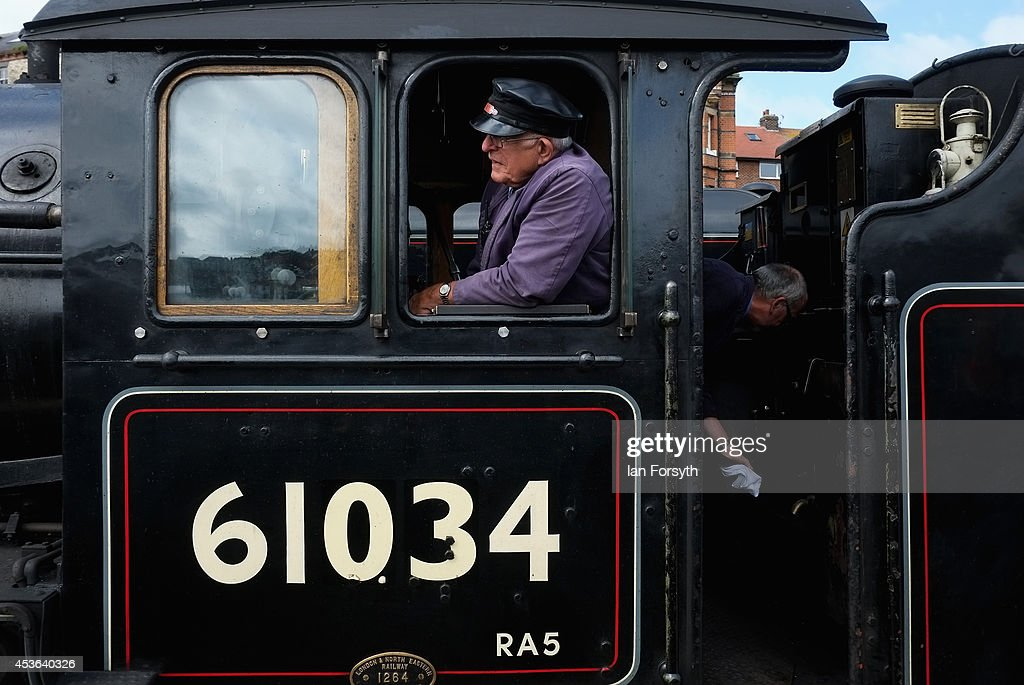 Engine driver Gerry Skelton drives the locomotive 'Chiru' during a ceremony to mark a second platform opening at Whitby train station on August 15, 2014 in Whitby, England. The second platform will provide passengers with more options for travel to the Yorkshire seaside town on the North Yorkshire Moors Railway and was the first time in half a century two steam locomotives were side by side at the station.