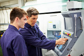 Trained Engineer And Apprentice Using Automated Milling Machine Together