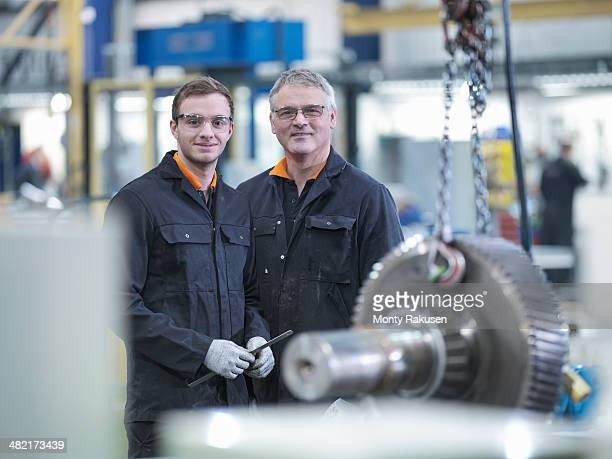 Engineer and apprentice with gear wheel at work station in factory, portrait