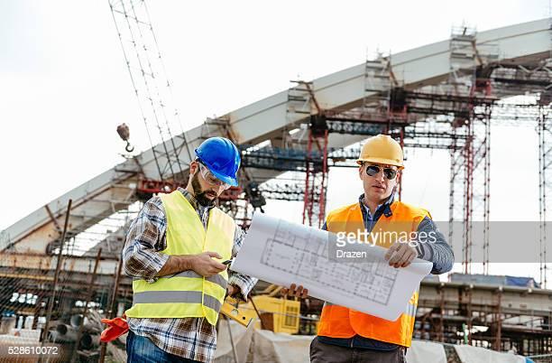 Gestionnaire de construction et ingénieur regardant blueprint sur place