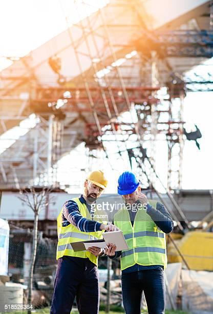 Ingenieur und Bau Website Manager um Pläne liegen vor, und plant