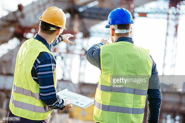 Engineer and contractor having brief meeting on construction site