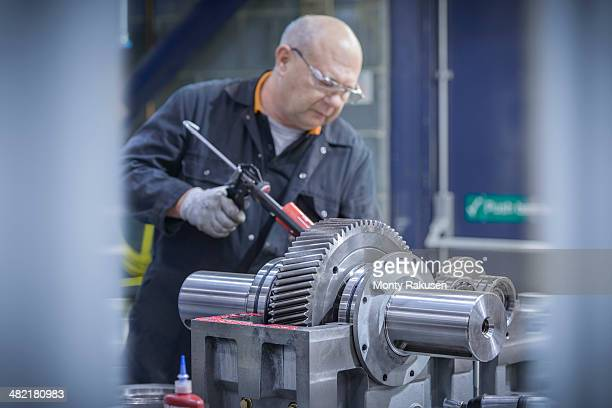 Engineer applying sealant to  industrial gearbox in factory