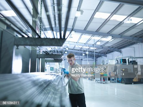 Engineer apprentice inspecting steel rods in factory