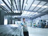 Engineer apprentice inspecting steel rods in factory