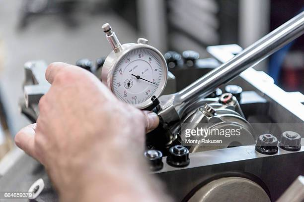 Engineer assembling engine in racing car factory, close up