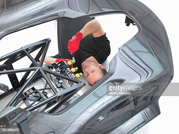 Engineer assembling supercar in sports car factory, overhead view