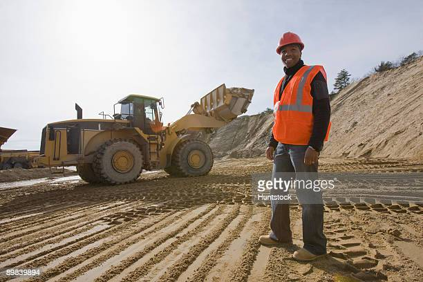 Engineer at a construction site with a front-end loader in the background