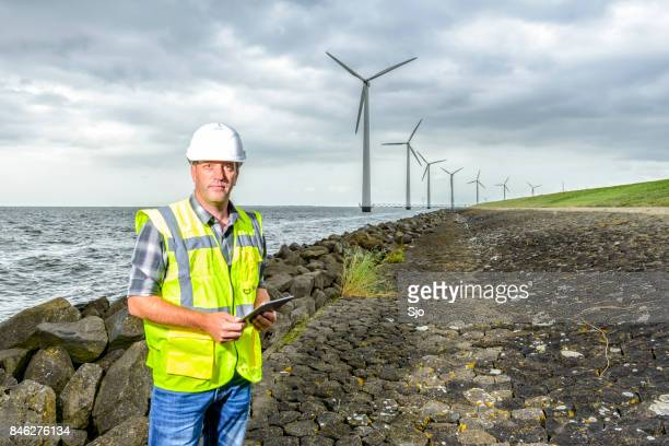 Engineer at an offshore wind turbine park during an overcast day