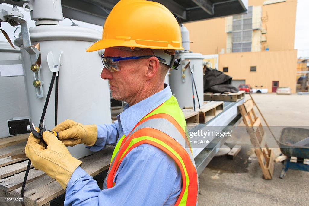 Engineer at electric power plant at storage area for transformers