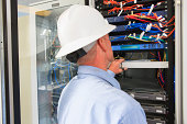 Engineer at electric power plant control room looking at servers and switches
