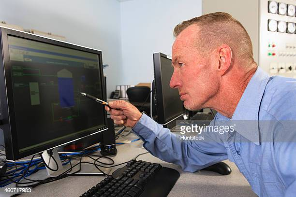 Engineer at electric power plant control room reviewing readings at management displays