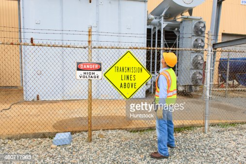 Engineer at electric power plant looking at transmission lines at transformer