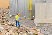 Engineer at electric power plant standing near water storage tank