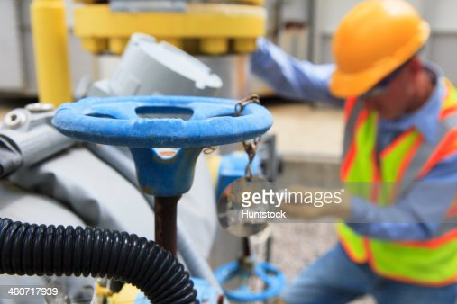 Engineer at electric power plant working with manual valves