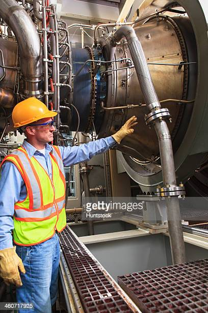 Engineer at fuel ignition stage of gas turbine which drives generators in power plant while turbine is powered down