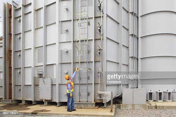 Engineer at sound suppression stage of gas turbine which drives generators in power plant
