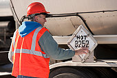 Engineer changing materials safety sign on tanker truck