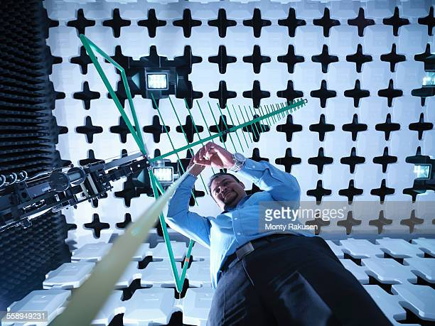 Engineer checking a bilog antennas height for electromagnetic compatibility (EMC) radiated immunity testing in a semi anechoic chamber, low angle view