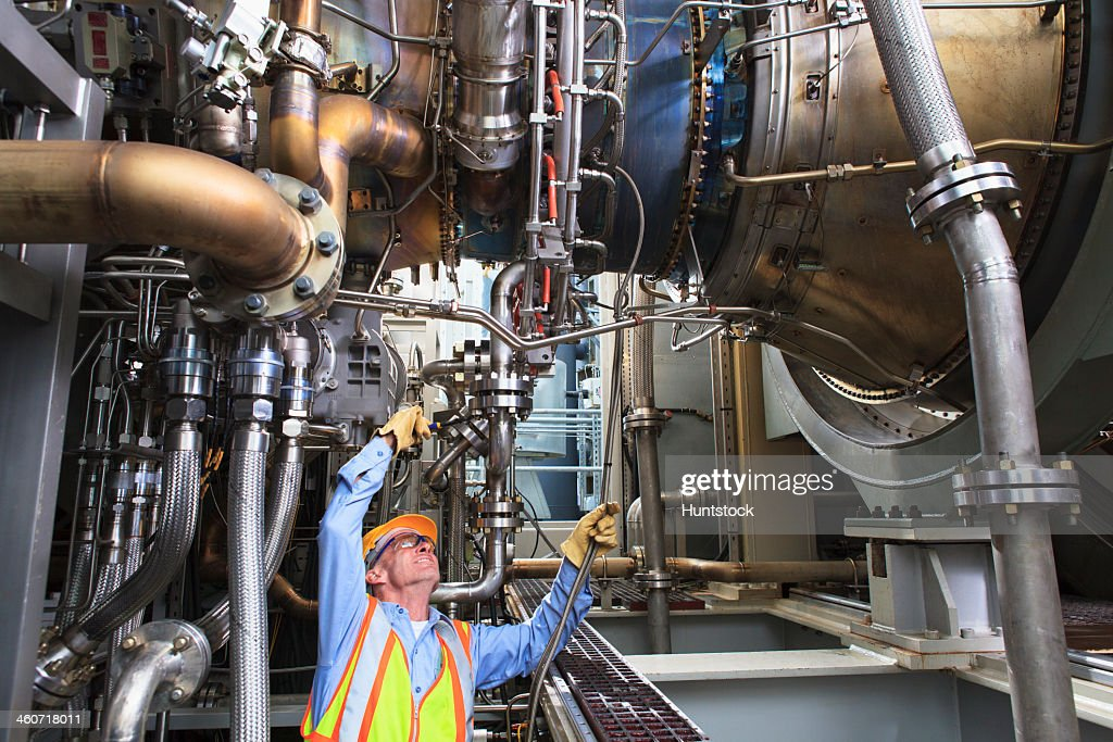 Engineer examining instrumentation cables at fuel injection stage of gas turbine which drives generators in power plant while turbine is powered down