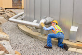 Engineer examining pipeline of water storage tank at electric power plant