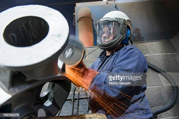 Engineer grinding unfinished casting in foundry