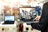 Engineer hand using laptop with machine real time monitoring system software. Blur automation robot arm machine in smart factory Industry 4th iot , digital manufacturing operation technology concept.