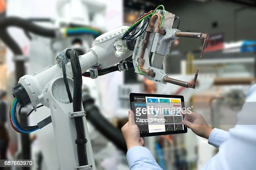 Engineer hand using tablet, heavy automation robot arm machine in smart factory industrial with tablet real time monitoring system application. Industry 4th iot concept. : Foto de stock