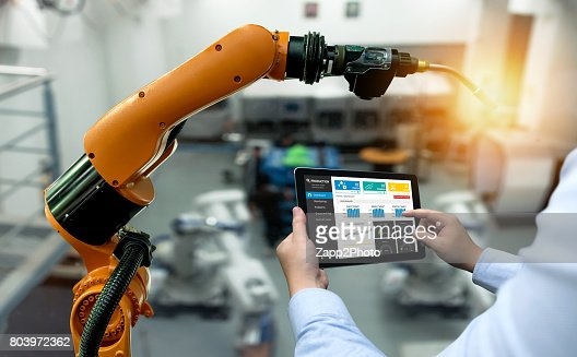 Engineer hand using tablet, heavy automation robot arm machine in smart factory industrial with tablet real time monitoring system application. Industry 4th iot concept. : Foto stock