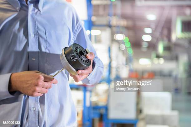 Engineer holding 3D printed exhaust valve actuator in factory