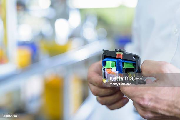 Engineer holding 3D printed parts in factory, close up