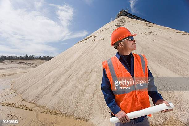 Engineer holding a blueprint at a gravel and asphalt plant