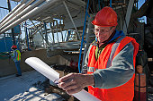 Engineer holding a blueprint at industrial plant