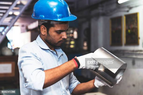 Engineer holding a sample piece of pipe