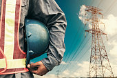 Engineer holding blue helmet standing on High-voltage tower