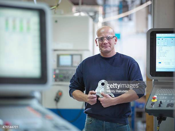 Engineer holding complex metal component in factory, portrait