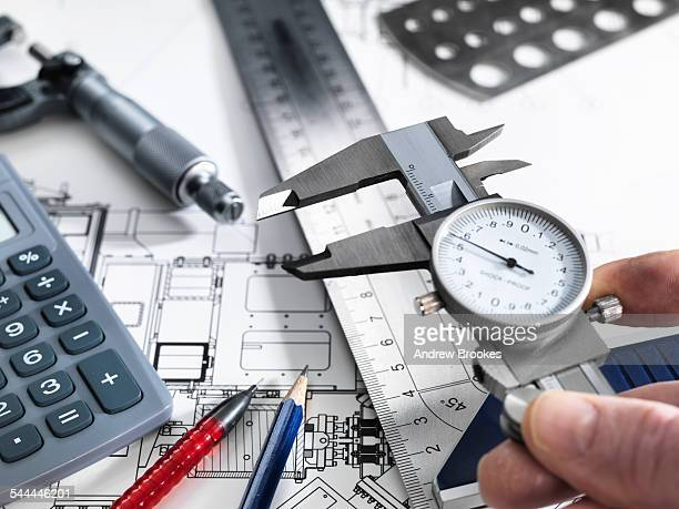 Engineer holding dial caliper with measurement equipment sitting on technical drawing