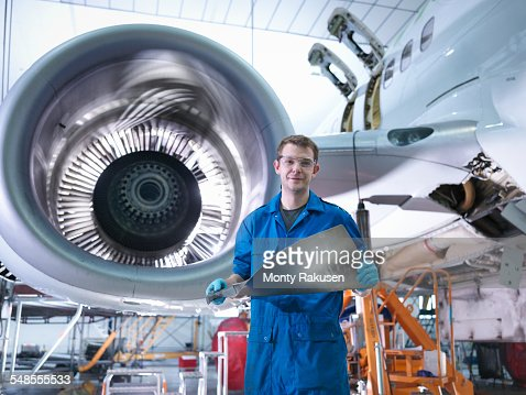 Engineer holding jet engine turbine blade in aircraft maintenance factory, portrait