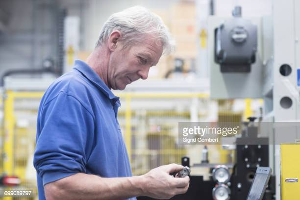 Engineer holding metal device in engineering plant