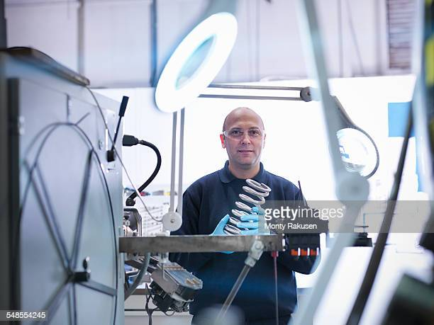 Engineer holding spring in automotive factory, portrait