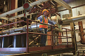 Engineer in electric power plant inspecting condenser room piping